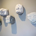 Stone sculptures hang on the wall in the introductory room of the museum.