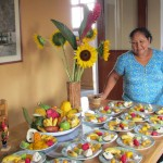 Alicia stands by a table full of Peruvian fruit, ready to share information and samples.