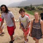 Josh, Phil and Haley walk up a sandy hill from the Supe Valley toward the Sacred City of Caral.