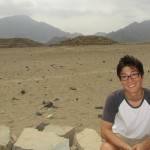 James rests on a rock near two of the Caral pyramids.