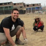 Zach helping a community gardener prepare soil for planting in Lima.