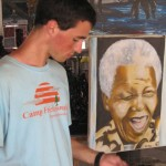 Matt next to a painting of Mwalimu Julius Nyerere, Tanzania's first president
